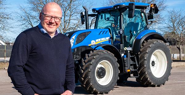 man står framför blå traktor